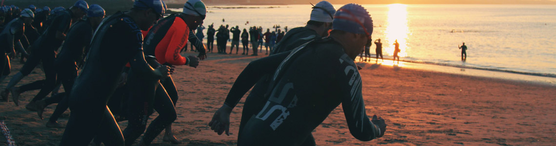 Swimmers race towards the water to launch the first leg of their triathlon.
