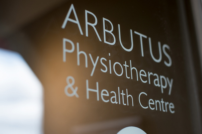 "Glass door with ""Arbutus Physiotherapy & Health Centre"" written on it"