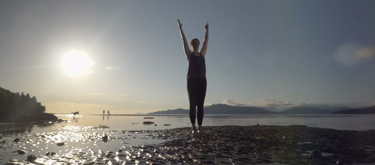 A woman stands tall on an ocean flood plain, doing yoga or stretching