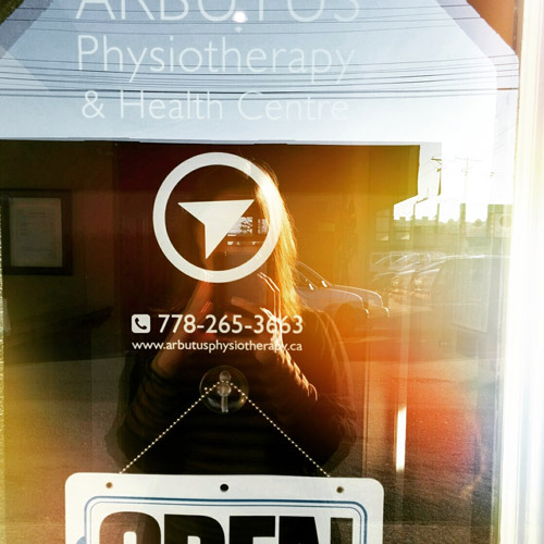 Olivia's reflection in the sunny door of the Arbutus Physiotherapy and Health Centre