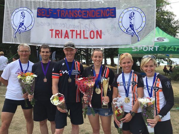 Sandy Wilson and others stand in front of the Self Transcendence Triathlon banner.