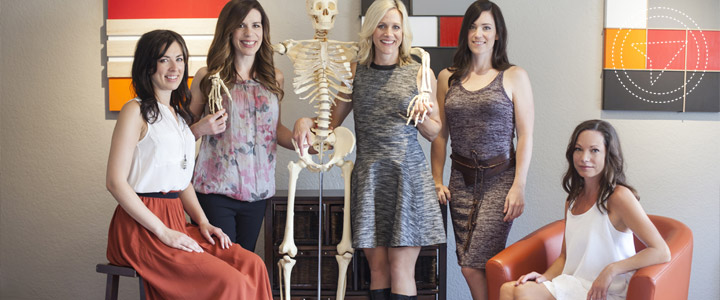 The team of practitioners at Arbutus Physio pose with a skeleton model.
