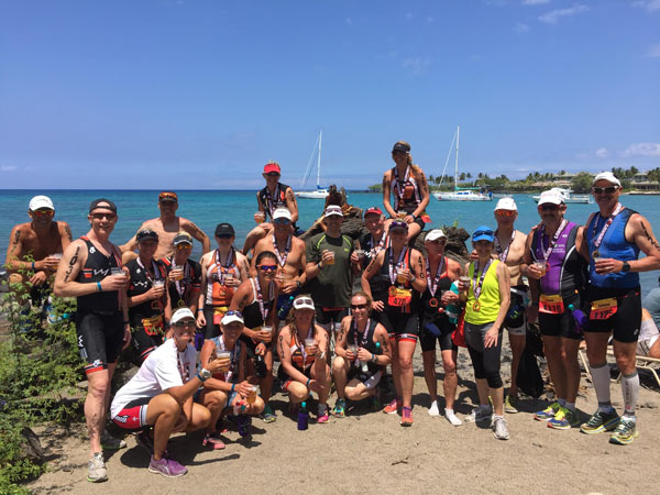 A team of triathletes pose in the sunshine beside the glistening ocean with their drinks and sunglasses