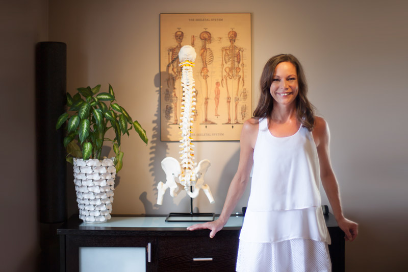 Dr. Hewstand stands in front of your vertebrae model in her clinic at Arbutus Physiotherapy