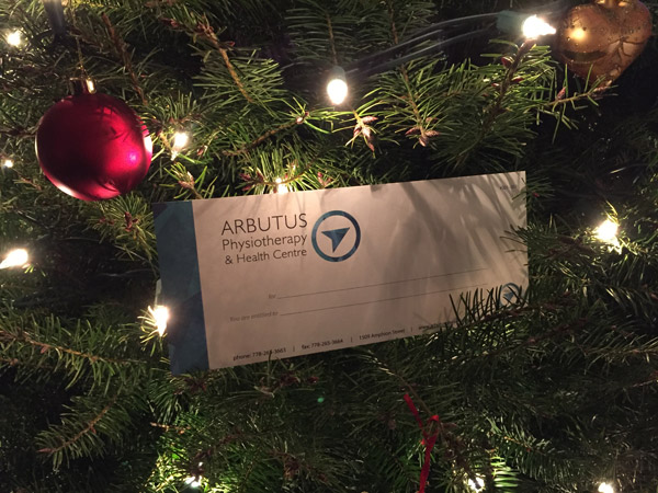 An Arbutus Health Clinic gift certificate rests on a Christmas tree.