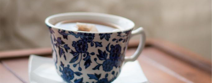 A hot drink steeps in delicate white and blue tea cup.