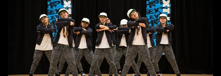 Hip hop dancers on stage breaking a move.