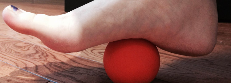 A foot rolls back and forth on a small red ball to relax the foot arch.