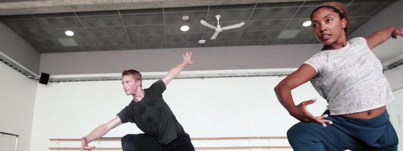 Dancers lunge in practice in a studio.
