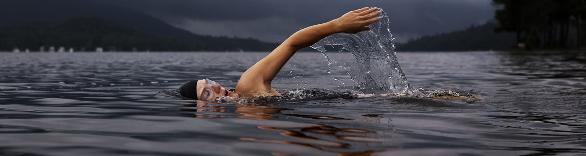 A swimmer takes a stroke on a dark cloudy day of lake training