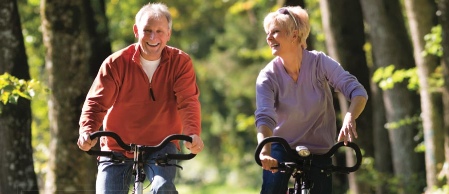 Two elderly people ride and laugh on their bicycles together