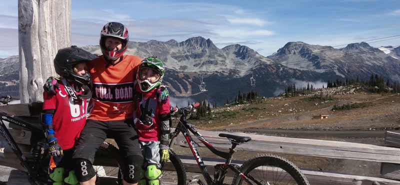 Dr. Alan Vukusic and his family pose in their mountain biking gear in the mountains of BC