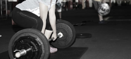 A weight lifter gets ready to perform a squat at the gym