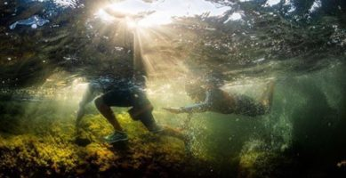 Racers in ÖTILLÖ SwimRun clamber over the rocks going from island to island