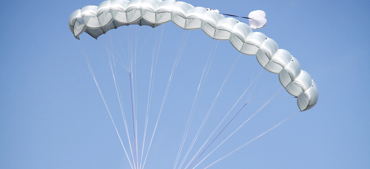 A parachute with many inflated cells moves through the air.