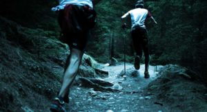 Two runners make their way up a hill cross country on a cold winter day in Victoria