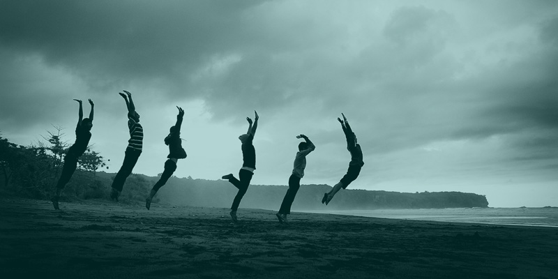 A group of people on the beach, jumping in sync and moving their bodies
