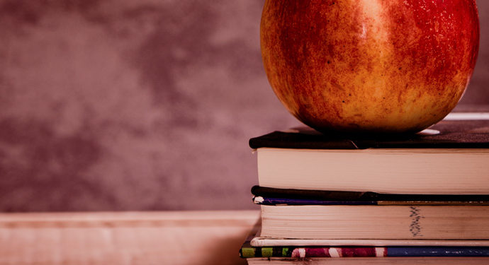 An apple stands on some books, on the teacher's desk. In Las Vegas!