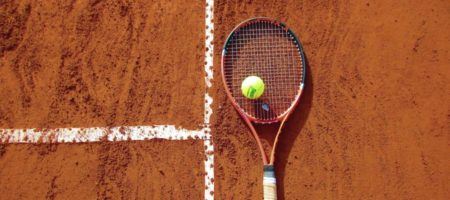 A tennis racquet lies on the clay court surface with a tennis ball on top.