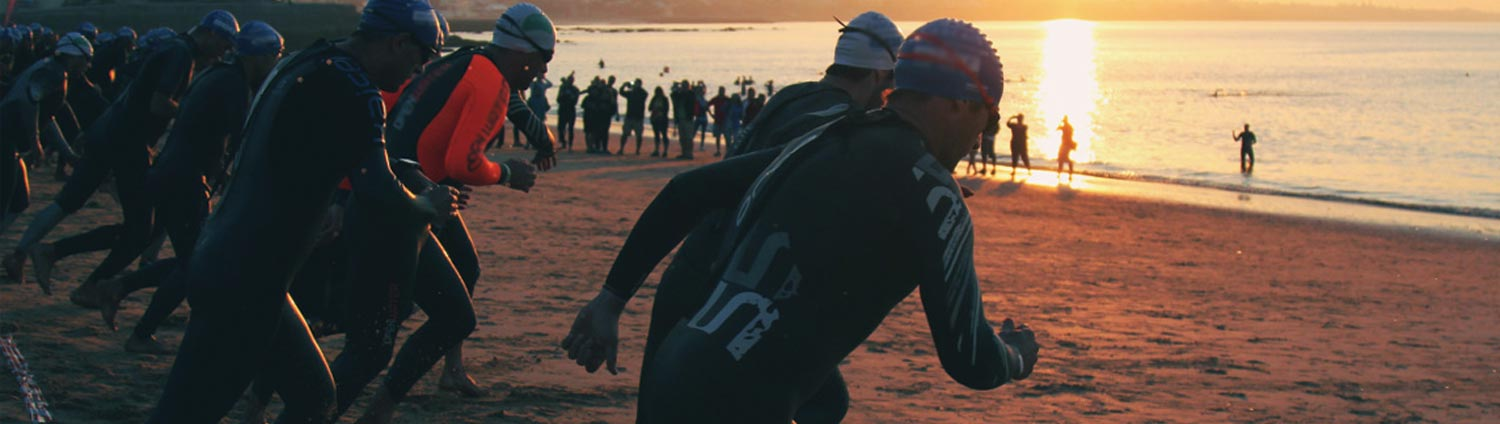 Triathletes race toward the water in the early morning light