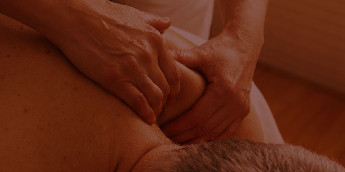 A massage therapist presses and holds the trapezius muscles around a patients back and neck.