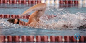 A swimmer takes a breath during the front crawl in a pool between lanes.