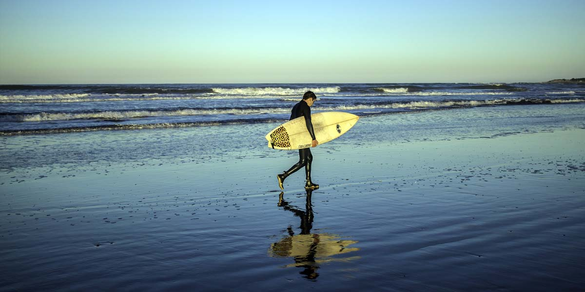 A surfer, a chiropractic surfer, walks out of the water with his surfboard.
