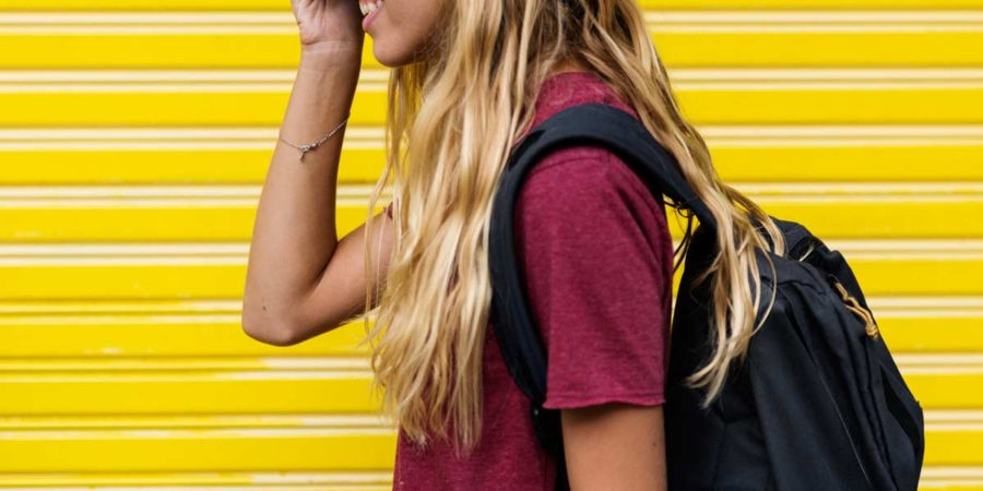 A girl wears a back pack that rests a long way away from her back.