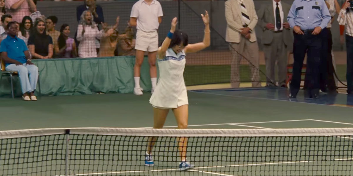 Billie Jean King throws her racquet in the air, on the tennis court.