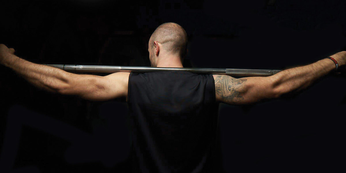 A weight lifter stands with the bar across his shoulders.