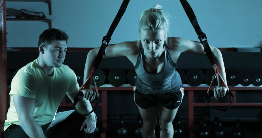 A woman does a strength building exercise at the gym while her coach watches carefully.