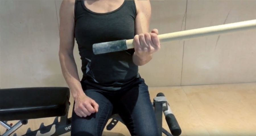 Christy Mader demonstrates a recovery exercise for climbers, from a sitting position with a long weight bar.