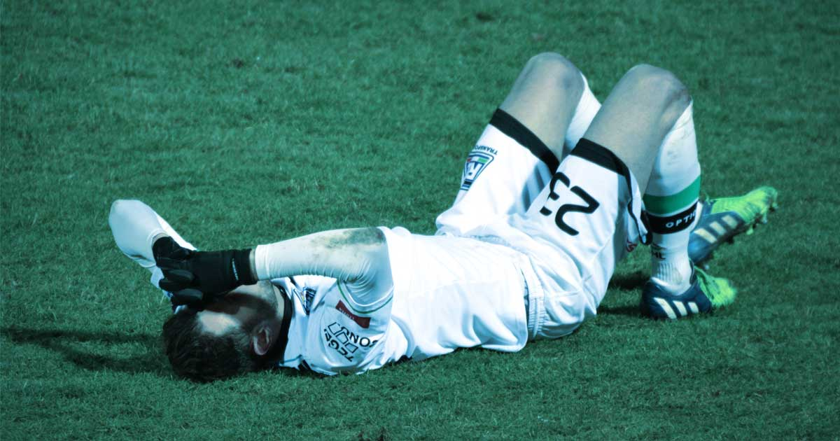 A soccer player lies down on their back on the football pitch grimacing in pain and grabbing their head due to a probable sprain