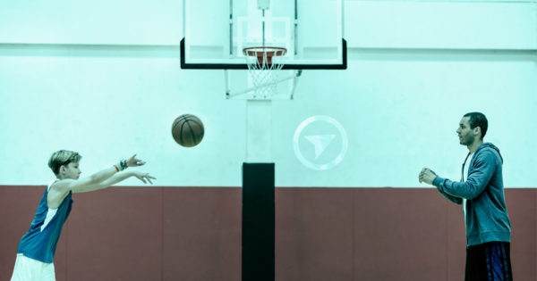 A basketball player throws the ball to his coach, who is recovery from a shoulder injury, underneath the basketball hoop.