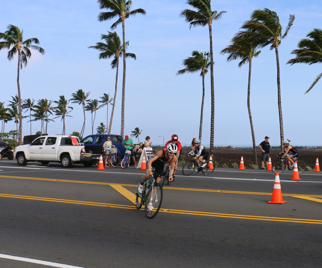 A woman on a bike making a sharp turn around orange cones in a race with palm trees blowing in the background.