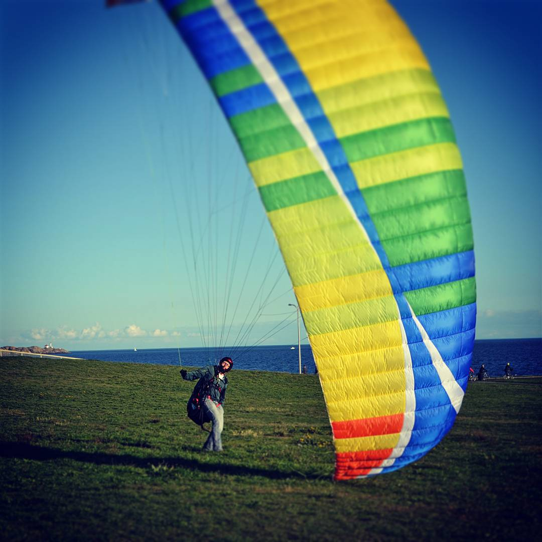 A man near clover point with a large blue, green, yellow, and red kite or sail about to go flying!