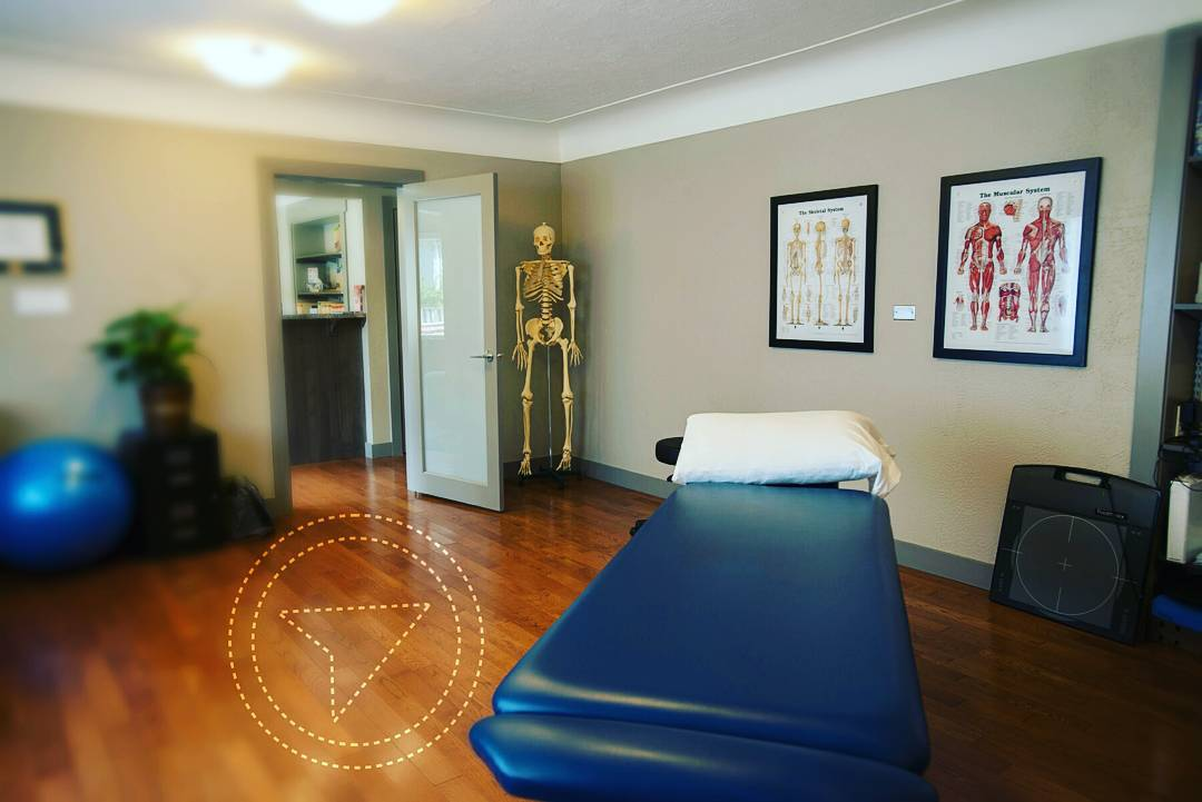 A photo of a room with a blue treatment bed on the front right and a skeleton in the back left. There are also two anatomical posters on the back wall.