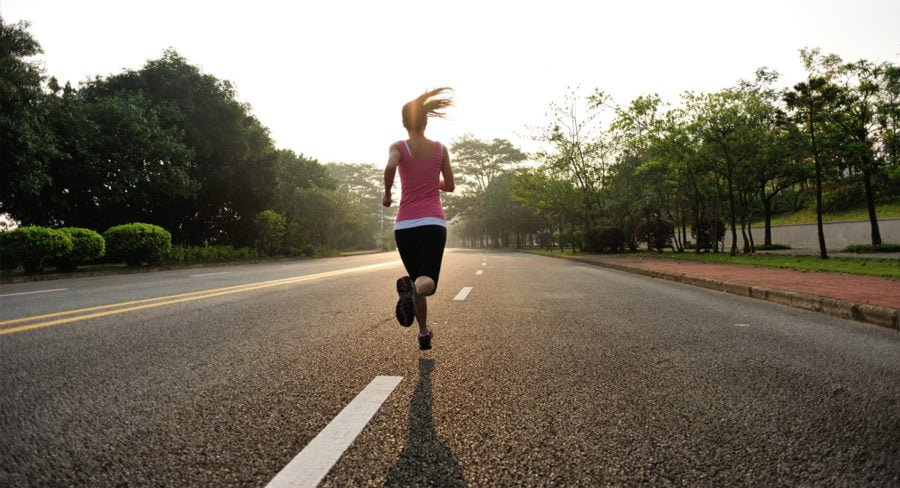 A woman runs down the middle of the road during a half marathon.