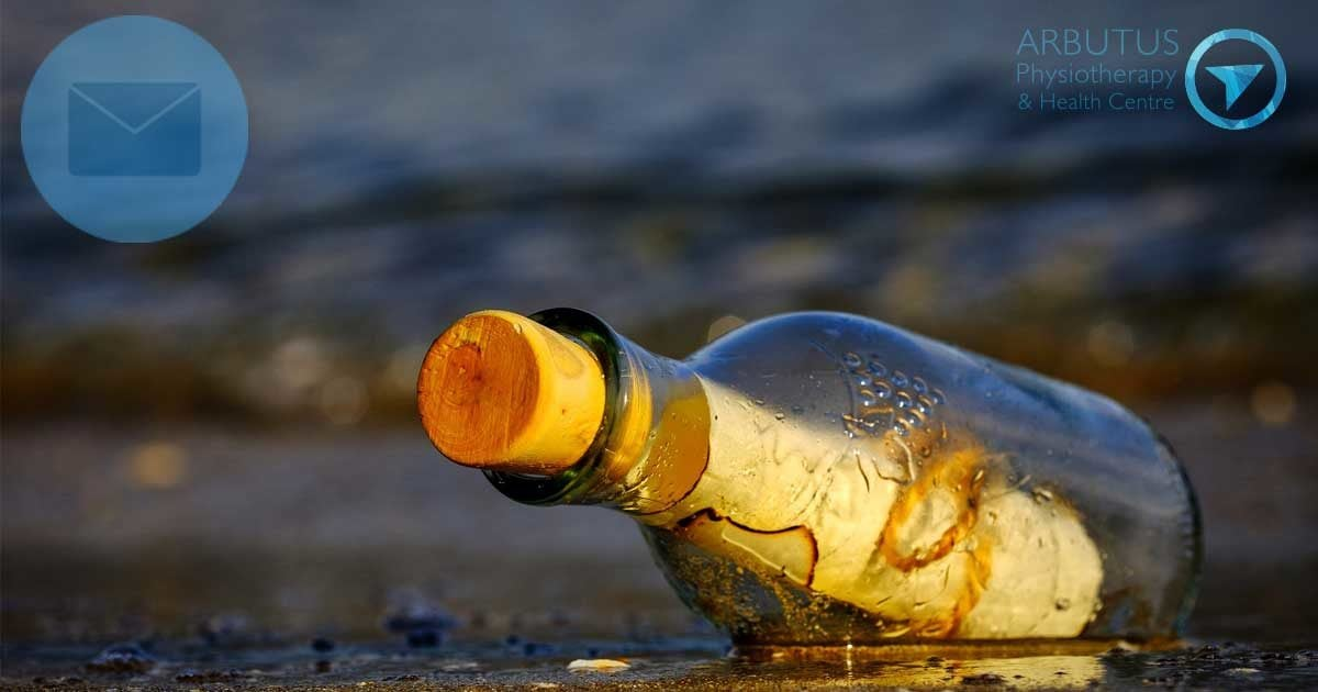 A message in a bottle, resting in the intertidal zone of a Pacific Northwest beach.
