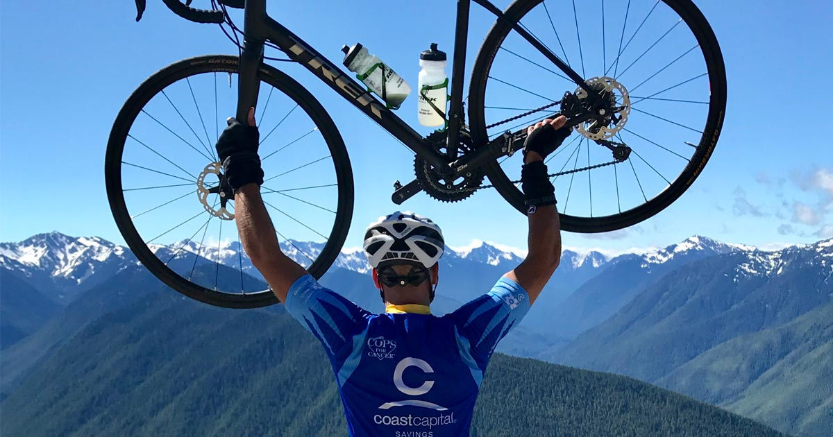 Jay Kreiger holds his bike up at the top of the rock on Vancouver Island.