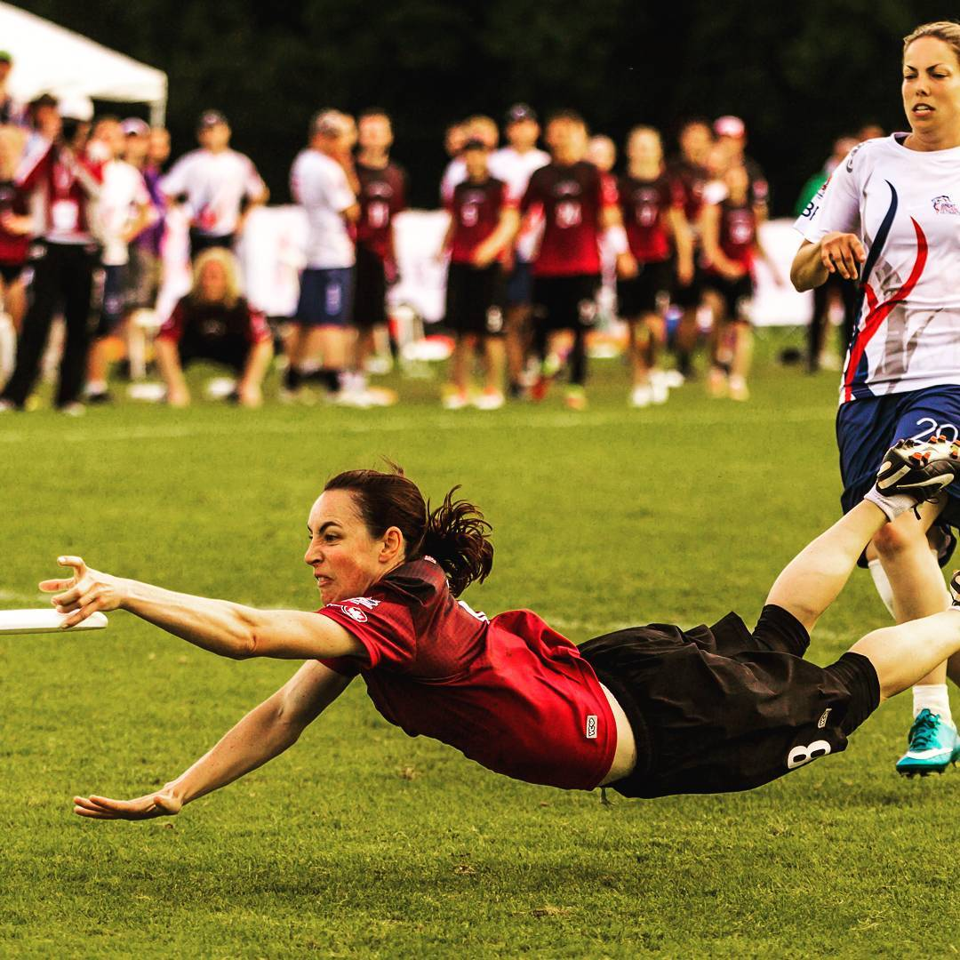 This is a photo of an Ultimate player diving for a frisbee in a red jersey and black shorts. She is almost at the ground with her arms stretched out and her legs behind her.