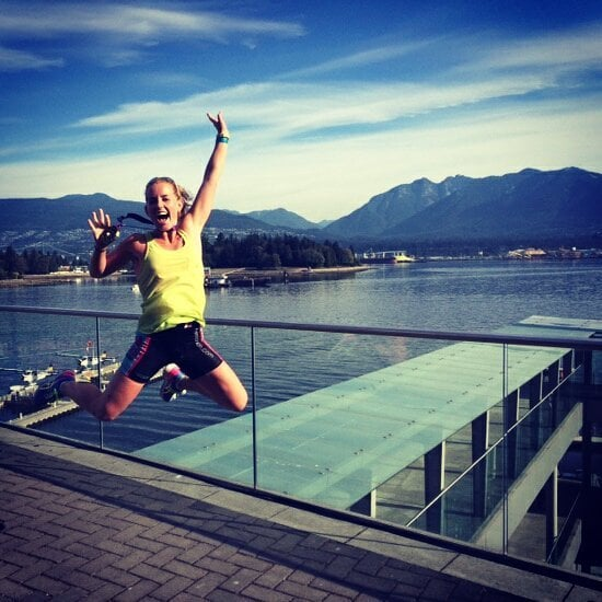 This is an image of Sophia, who is left of center, jumping and pumping her left fist into the air. She is on a walkway above a pier with ocean and mountains behind her. She is wearing a yellow running tank and black shorts.