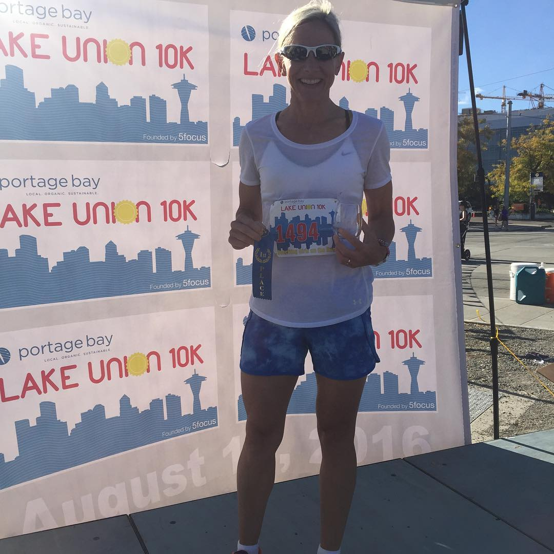 "This is a photo of a woman in sunglasses, a white tee shirt, and blue shorts. She is smiling and holding her race number in front of a ""Lake Union 10k"" back drop. It is a blue clear day."