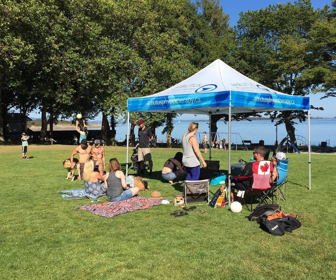 This is a photo of the arbutus team outside on the grass in front of Willows Beach. It is a sunny day, and they are under a white and light blue arbutus physio tent.