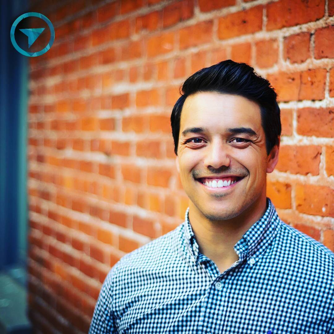 This is a photo of Mike standing in front of a brick wall smiling widely in a light blue dress shirt with small white dots. He has smooth, short black hair.