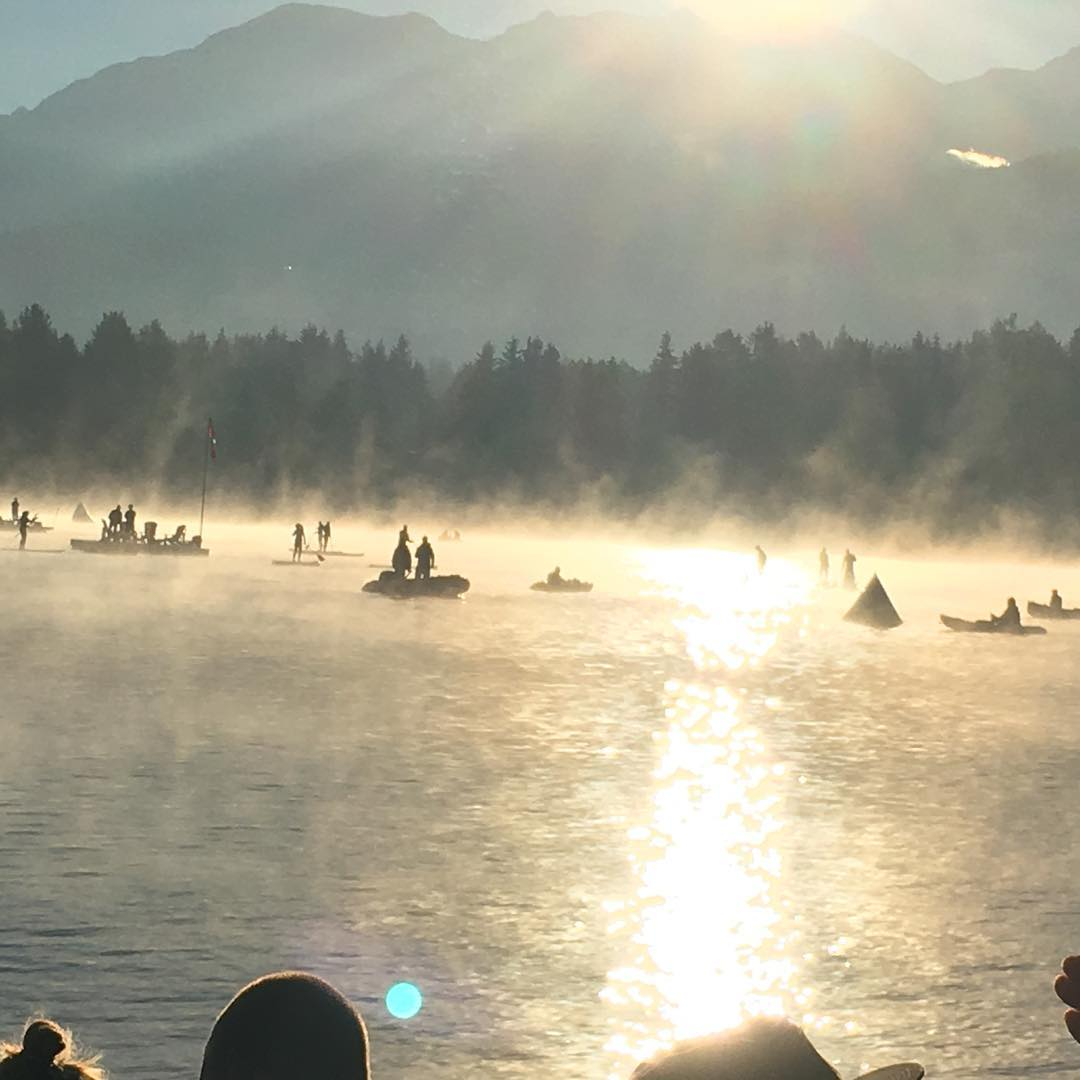A lake in Whistler, with fog rising and swimmers and boats ready to go.