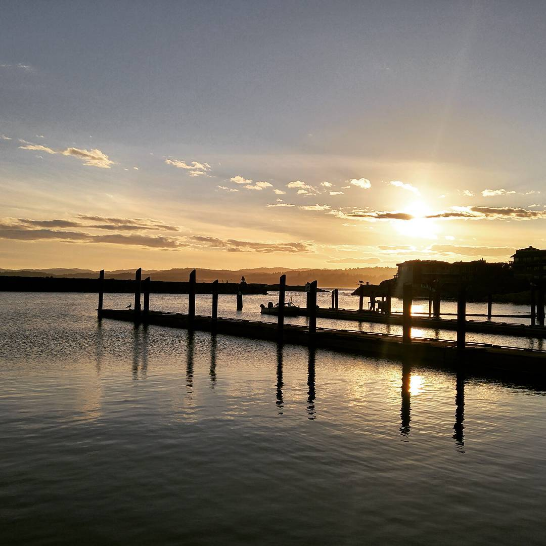 This is a photo of a sun setting on the water behind two docks with one behind the other. It is a clear sunset and the docks are just silhouettes against the sun.