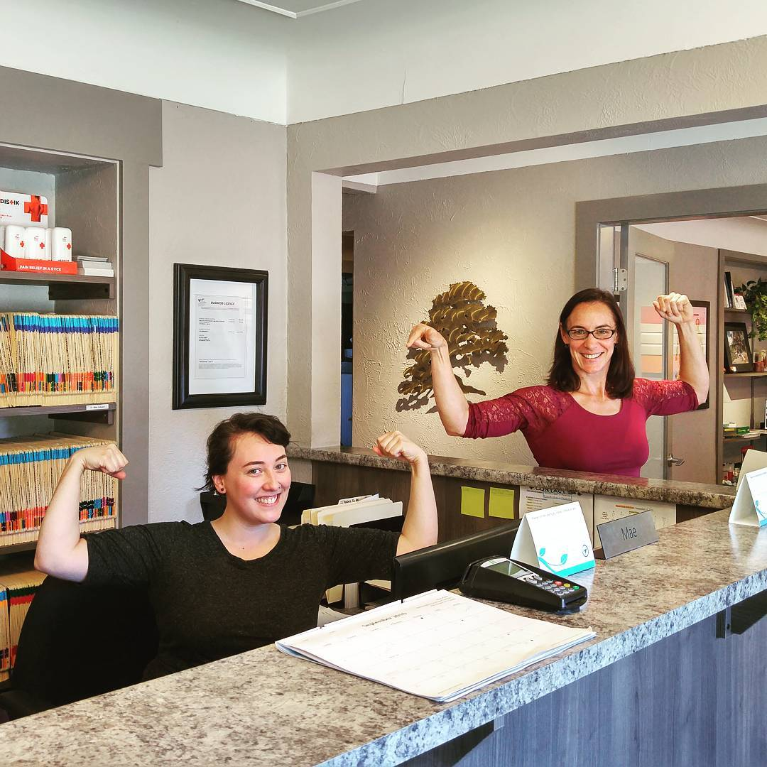 This is a photo of two women in an office flexing both their arms upwards. One is sitting behind a desk, and the other is standing beside it. Both are smiling.