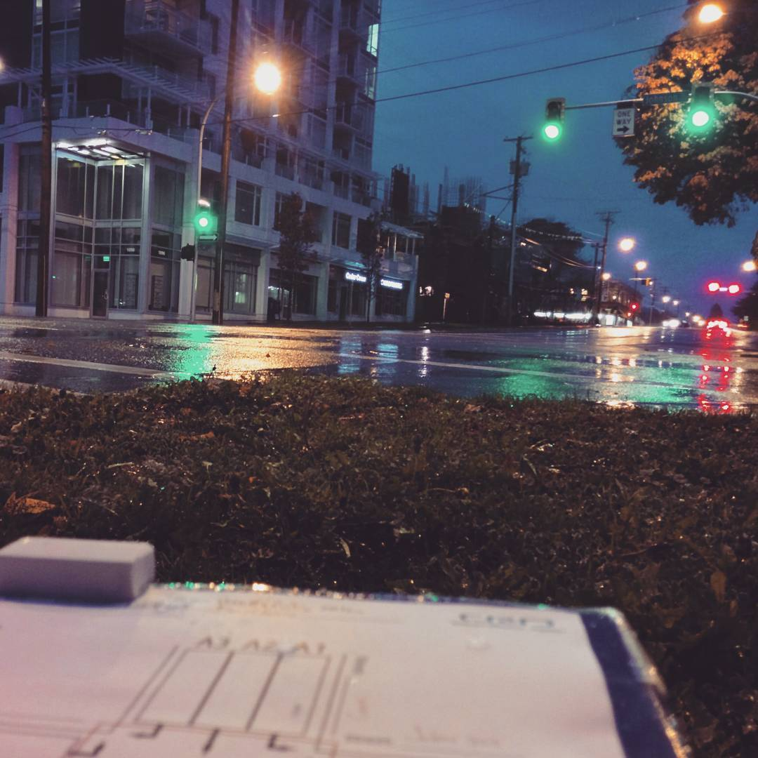 This is a photo taken in the dusky early morning outside. It looks out onto a road that is glistening with rain water, and traffic lights. There is a chart on a clipboard in the bottom left corner.