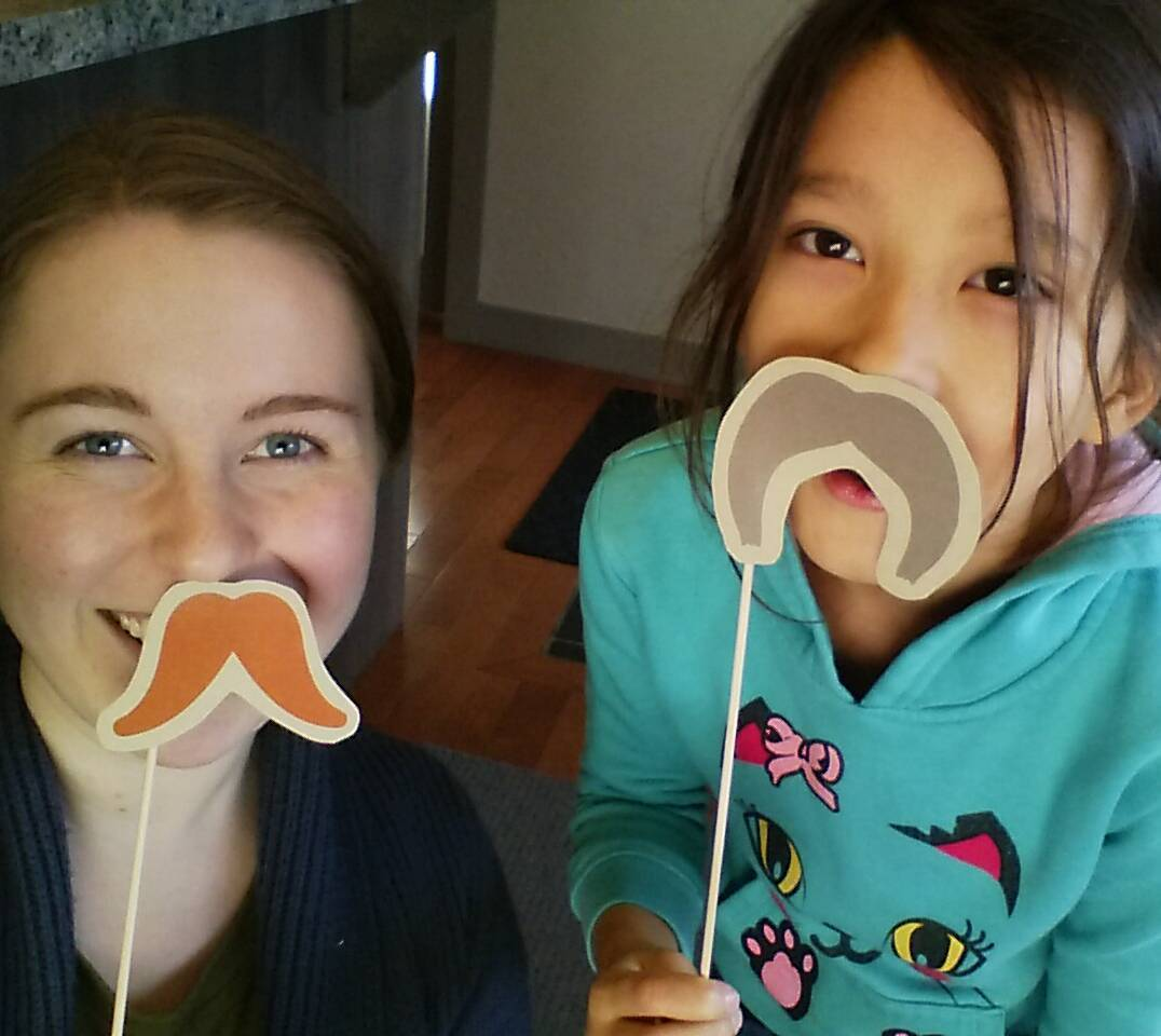This is a photo of two young girls smiling and holding up paper cut out moustaches up to their mouths. They are inside and looking up at the camera. One of the moustaches is orange a curls up at the bottom and the other is grey and sags downwards.